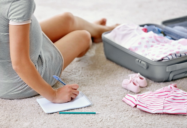 Pregnant Woman Packing Her Suitcase for the Maternity Hospital Stay When She Goes Into Labor