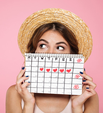 Woman Tracking Her Period on a Calendar