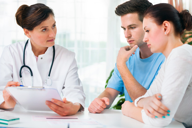 Doctor Consulting with Couple About Fertility Treatment Options